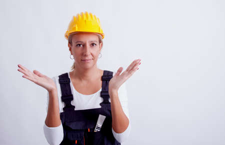 Female construction worker with tools on white  photo