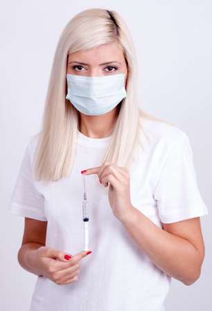 Female doctor or nurse in medical mask holding syringe with injection photo