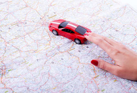 Toy red car on female hand on white background photo
