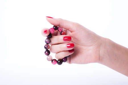 Beautiful woman hands with red manicure holding color pearl necklace photo