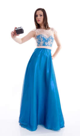 Beautiful woman in a blue dress shooting with an old camera photo