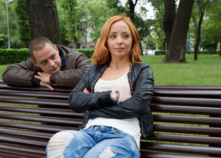 violencia intrafamiliar: Hombre joven y mujer enojada y conflictiva en un banco del parque Foto de archivo