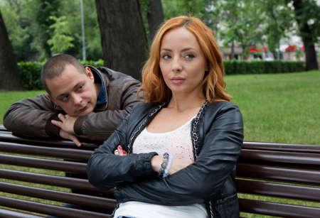 novios enojados: Hombre joven y mujer enojada y conflictiva en un banco del parque Foto de archivo