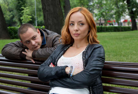 man and women: Young man and woman angry and conflicting on a park bench