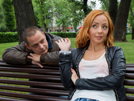 conflicting: Young man and woman angry and conflicting on a park bench
