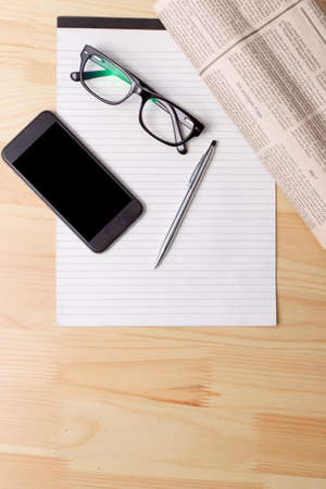 broadsheet newspaper: Newspapers and coffee cup, reading glasses, pen and striped paper.