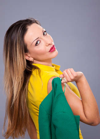Portrait of beautiful woman in yellow dress on a gray background