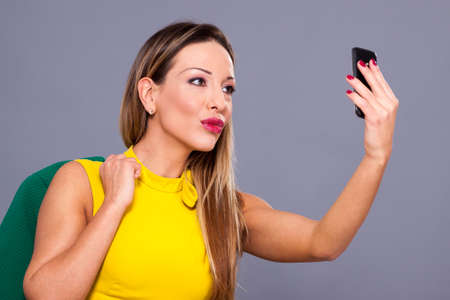 Portrait of beautiful woman in yellow dress on a gray background makes his selfie Stock Photo