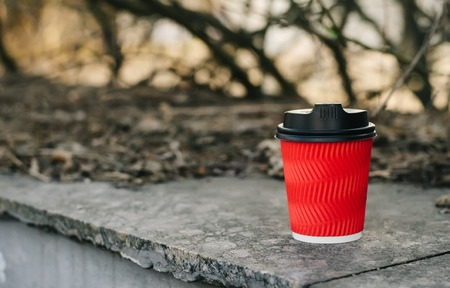 Red Cup of coffee to go on a blurry background