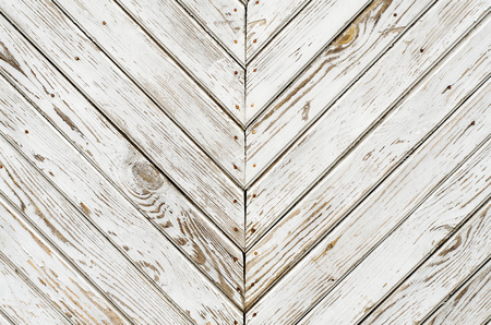 Texture of the old wooden gate which is covered with shabby white paint. Oblique lines mirrored. Archivio Fotografico