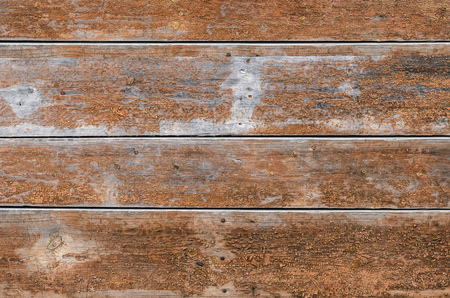 Old wooden fence made of wide boards of brown color with rusty nails. Texture. Simply background.