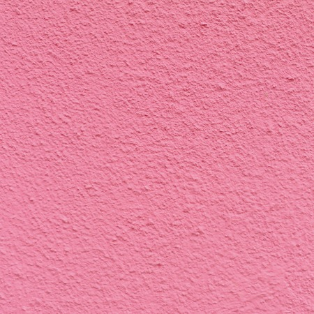 The old wall of the apartment house in pink color. Texture of the peeled surface.