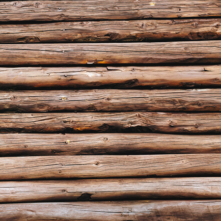 Old wooden logs background. Weathered wooden wall in brown color. Archivio Fotografico