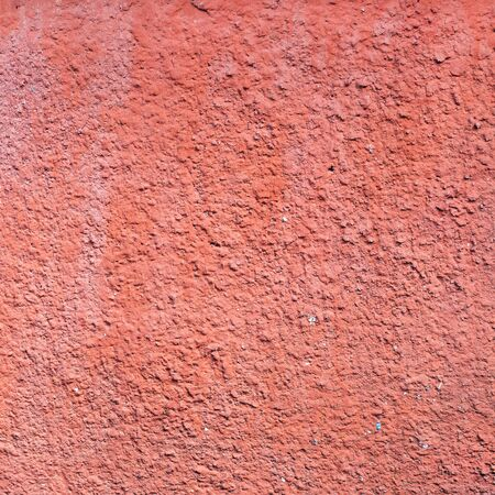 The old wall of the apartment house is red. Texture of the peeled surface.