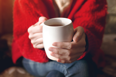 Closeup of female hands with a cup of beverage. Beautiful girl in red sweater holding cup of tea in the morning sunlight.