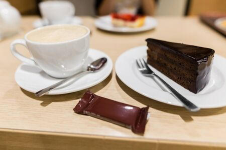 Traditional austrian sachertorte on plate on wooden background. Chocolate cake and a cup of coffee.