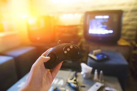 A young man holding game controller playing video games. Oldschool console. Gaming concept.
