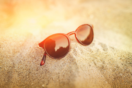 Sunglasses on the golden sand with reflections in the glass. Seascape ocean and beautiful beach paradise. Summer vacation concept. Close up. Archivio Fotografico