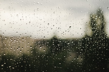 Raindrops on window with blurry trees as background. Rainy season. Creative abstract background.