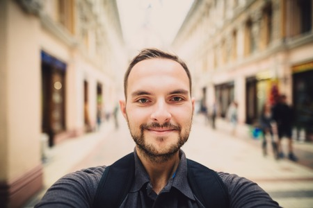 Portrait of a happy man with beard taking selfie. Hipster tourist smiles into the camera. Blurred background. Archivio Fotografico