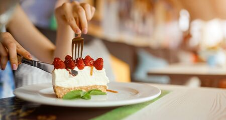 Womans hands holding a plate with slice of strawberry cheesecake. Girl hands cut the cake by fork. Banco de Imagens