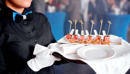 woman waiter with tray with canape on white napkin