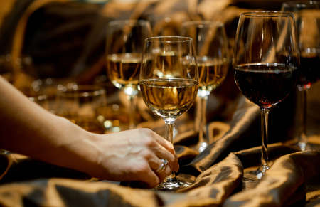 wine glasses with white and red wine on the table decorated with gold cloth. A womans hand holds one glass.