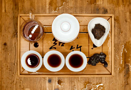 Chinese traditional tea tray with dragon on tray and filled kettle cups top shoot