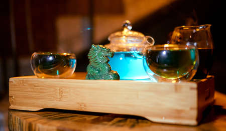 Chinese traditional tea tray with dragon in the foreground, hookah tube and kettle cups