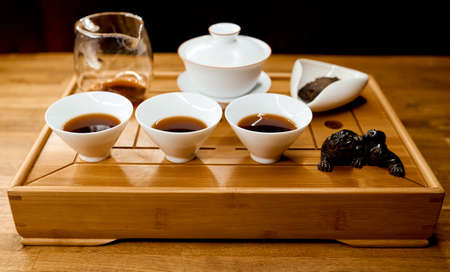 Chinese traditional tea tray with dragon on tray and filled kettle cups
