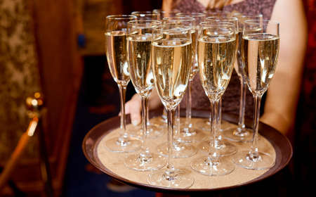 Full glasses of champagne on tray which hold waiter