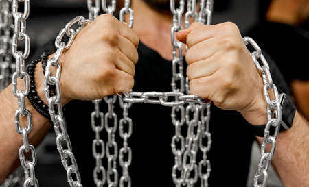 Mens hands try to break the chain test for strength