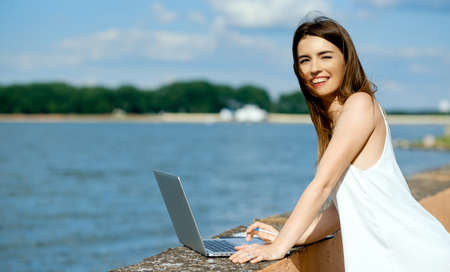 beautiful, smiling woman in a white dress with a tablet, pen, laptop phone on the dock Stock Photo