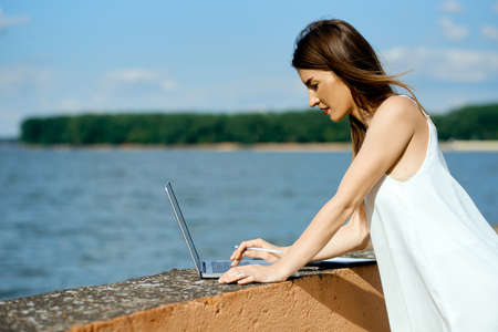 beautiful, serious woman in a white dress with a tablet, pen, laptop phone on the dock Stock Photo