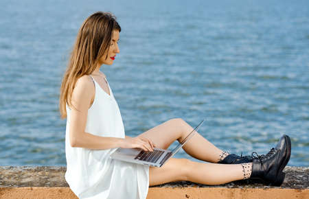 Businesswoman comfortably positioned on a concrete fence berth works behind a laptop