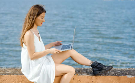A woman prepares to work behind a laptop sitting on a concrete pier with her leg dangling