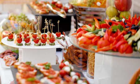 Catering. The table is richly richly filled with various snacks and vegetables. Focus on tomato and cheese snacks. High quality photo