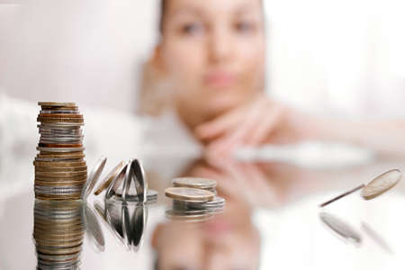 woman look on pile of coins, column of coins falls , business crisis concept. shallow focus