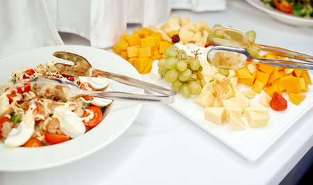on the table cheese plate with grapes and salad with egg meat and tomatoes 免版税图像