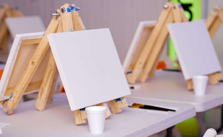 several easels prepared for a lesson with a set of brushes Archivio Fotografico