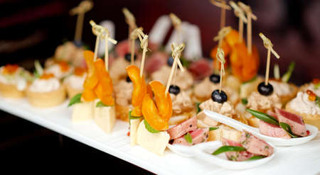 catering made canapes of cheese and orange and pieces of meat on spoons