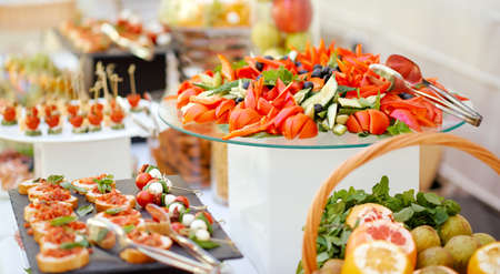 a covered self-service table organized catering with fruit vegetables and sandwiches
