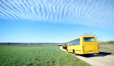 yellow old broken bus stands on a sandy road in a green field under the wind clouds Standard-Bild