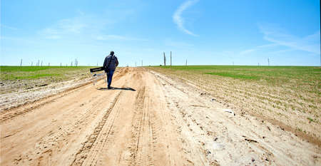 Lonely unmarked man with a production chair walks away on an old broken road