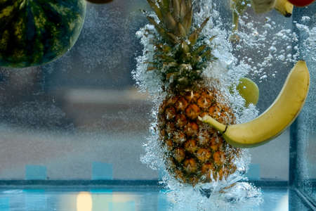fruit pineapple and banana thrown into the water, bubbles appeared