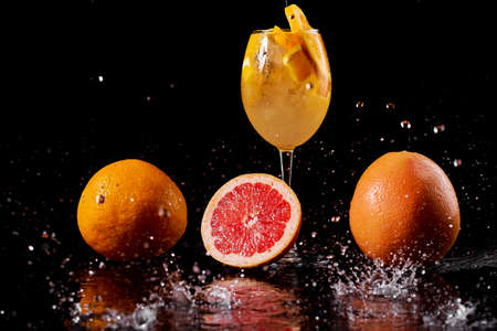 orange cocktail in a glass on a black background with grapefruit on a wet table with spray