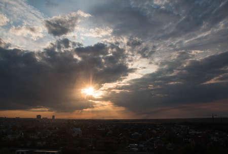Paysage d'été. En position horizontale. Ciel rose dans les rayons du soleil couchant. Photographié à un grand angle. Horizon. Au fond, une grue de chantier. La campagne. Coucher de soleil.