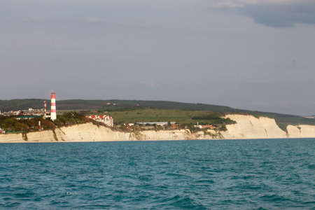 Coastal lighthouse on the edge of a rocky promontory in the black sea, the city of Gelendzhik. Located to the left of the frame. Landscape. Horizontal photo. Blurred background. Summer. opy space.