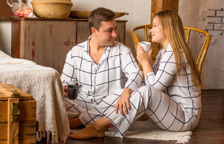 A couple in love of European nationality. With smiling, happy faces sitting on the floor, in their pajamas. They hold mugs in their hands. Horizontal photo.