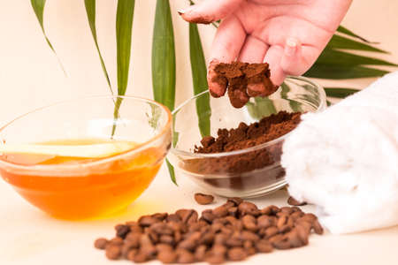 Spa care at home. A womans hand holds ground coffee. Scrub of coffee and honey. Bright background. Space for text. Horizontal photo. The view from the top. 写真素材